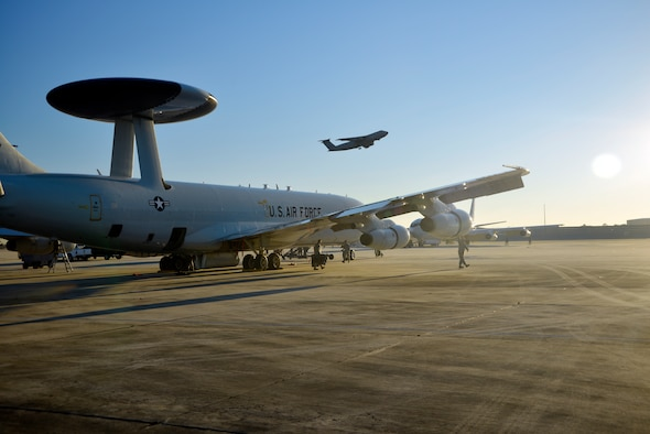 An AWACS E-3 aircraft sits on the runway at Robins Air Force Base, Ga., as a C-5 takes flight overhead. The E-3 was at Robins prepping for participation in the Composite Unit Training Exercise of the east coast with sister services the Navy and Marines. (U.S. Air Force photo by Ed Aspera)