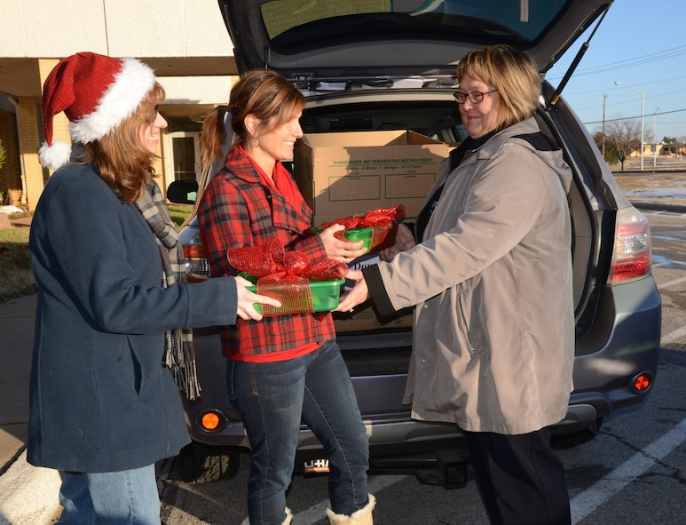Lisa Wood, left, and Theresa Humphrey accept cookies and brownies from Rosemary Herman for the annual Team Tinker Cookie Drive on Dec. 11. Nearly 6,000 cookies were bagged and delivered to single Airmen living in the dorms. (Air Force photo by Kelly White)