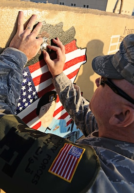 Chief Master Sgt. Dewey Hansford, 386th Expeditionary Security Forces Squadron chief manager, donates his SFS badge to a 2005 tribute painting of Airman 1st Class Elizabeth Jacobson, undisclosed location Southwest Asia. After noticing sun damage and chipped paint Moore decided to resuscitate the beauty it once had. She is the first Security Forces Airman to die in Operation Iraqi Freedom. She is also the first female Airman killed in the line of duty in support of OIF. (U.S. Air Force photo by Senior Airman Desiree W. Moye)