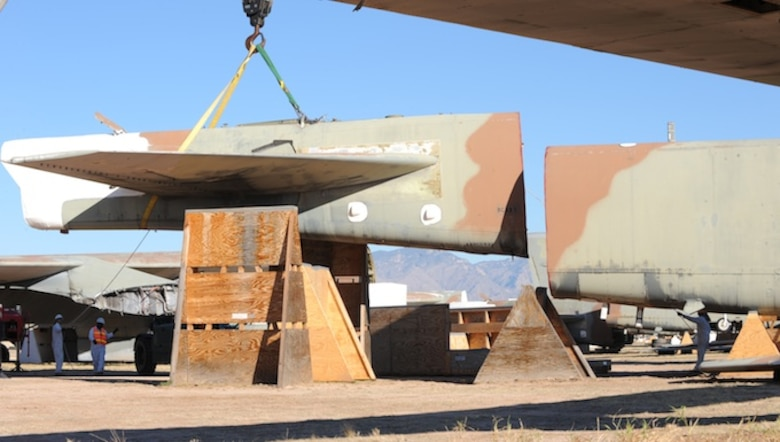 Personnel with the 578th Storage and Disposal Squadron lift a B-52G's tail section onto a custom-made cradle Dec, 19, 2013, at the 309th Aerospace Maintenance and Regeneration Group, Davis-Monthan Air Force Base, Ariz. The cradle is purposely placed 30 degrees off center and a minimum of six feet apart from the aircraft's fuselage in order for Russia's satellites to verify the elimination. (U.S Air Force photo/Staff Sgt. Angela Ruiz)