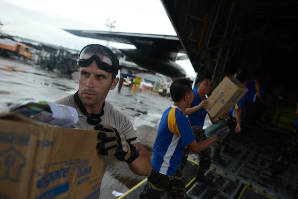 Tech. Sgt. Joe Klimaski, 736th Security Forces Squadron squad leader, offloads relief supplies from a Philippine Air Force C-130 aircraft with Philippine airmen in support of Operation Damayan in Tacloban, Philippines, Nov. 23, 2013. (U.S. Air Force photo by 2nd Lt. Jake Bailey/Released)