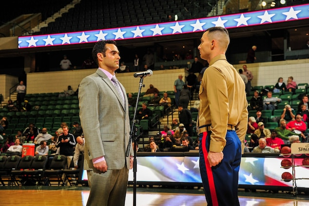 U.S. Marine Corps Capt. Nathan Harmon, Recruiting Station Detroit's Officer Selection Officer, administers the oath of enlistment to Shane Azizi during half time at Eastern Michigan University men's basketball game against the University of Massachusetts Dec. 3, 2013. Azizi was one of 38 individuals selected for a reserve contract, and he is slated to attend Officer Candidates School January 2014. (U.S. Marine Corps photo by Sgt. Elyssa Quesada/Released)