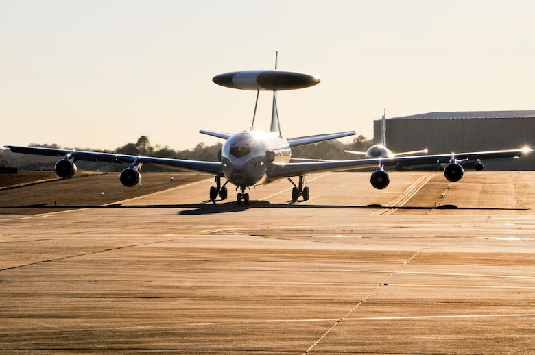 An E-3 Sentry AWACS taxis in after a mission with an E-8C Joint STARS following close behind at Robins Air Force Base, Ga., Dec. 12, 2013. The AWACS aircraft along with RC-135 RIVETJOINT aircraft were at Robins to participate in a command and control (C2) joint force exercise with Team JSTARS. The three platforms, known as the Iron Triad, participated in the exercise to practice interoperability between multiple C2 platforms. (U.S. Air National Guard photos by Capt. Pamela Stauffer/Released)
