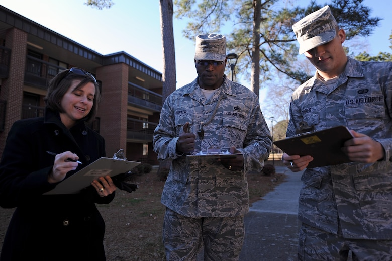 From left, Kirsten Pettus, wife of Col. Lamar Pettus, 4th Fighter Wing vice commander, Chief Master Sgt. Woodrow Carter, 4th Mission Support Group superintendent, and Airman 1st Class Devin Powner, 4th Contracting Squadron contract specialist, compare notes from the dorm room door decoration contest at Seymour Johnson Air Force Base, N.C., Dec. 18, 2013. Doors were judged on creativity and originality with prizes going to the top three contestants. (U.S. Air Force photo by Airman 1st Class Aaron J. Jenne)