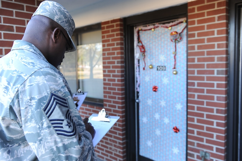 Chief Master Sgt. Woodrow Carter, 4th Mission Support Group superintendent, judges a contestant's entry during a dorm room door decoration contest at Seymour Johnson Air Force Base, N.C., Dec. 18, 2013. The contest was open to all dorm residents for a chance to win prizes such as movie tickets and gift certificates. (U.S. Air Force photo by Airman 1st Class Aaron J. Jenne)