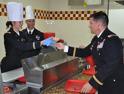 U.S. Army 2nd Lt. Lauren Rattan serves a shrimp cocktail to U.S. Army Lt. Col. Alan McKewan at the dining facility at Soto Cano Air Base, Honduras, Dec. 25, 2013.  Members of Joint Task Force-Bravo were treated to a Christmas Day meal with all the trimmings today.  Leadership from across Joint Task Force-Bravo, to include the Army Support Activity, Army Forces Battalion, Joint Security Forces, 612th Air Base Squadron, 1-228th Aviation Regiment, and Medical Element wore their dress uniforms and served the members of the Task Force. (U.S. Air Force photo by Capt. Zach Anderson)
