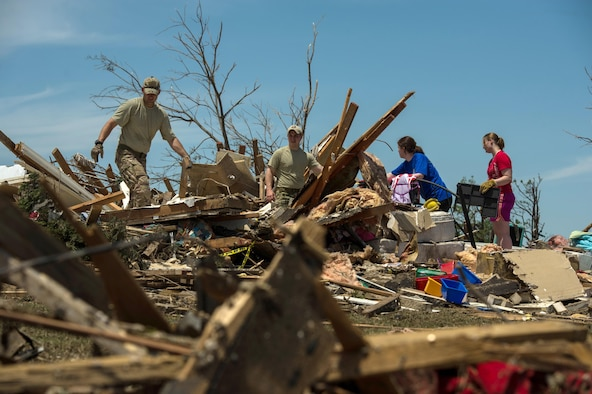 Capt. Van Blaylock (left) and Senior Airman Joshua Jacobs help resident Alyson Tinney and Elise Hopkins search through the debris looking for salvageable items May 22, 2013, in Moore, Okla. On May 20, 2013, an EF-5 tornado, with winds reaching at least 200 mph, traveled for 20 miles, leaving a two-mile-wide path of destruction, leveling homes, crushing vehicles and killing more than 20 people. More than 115 Oklahoma National Guard members were activated to assist in the rescue and relief efforts. Blaylock and Jacobs are Joint Terminal Attack Controller assigned to the 146th Air Support Operations Squadron. (U.S. Air Force photo/Staff Sgt. Jonathan Snyder)