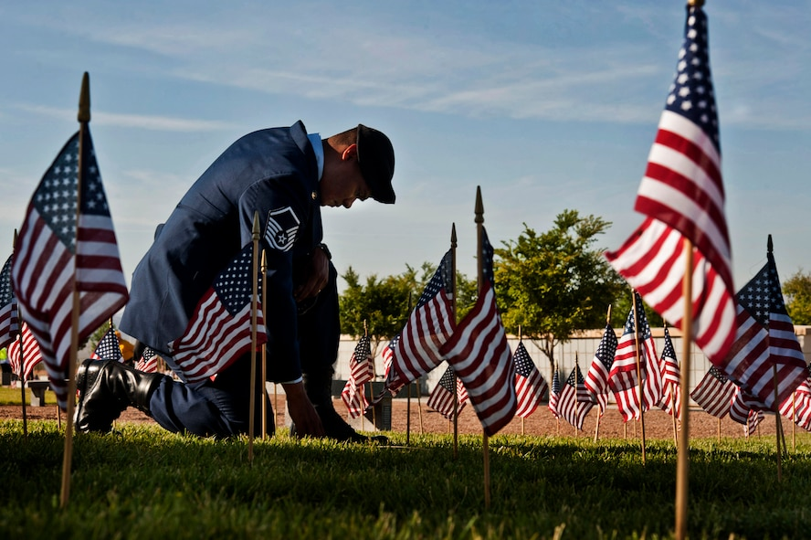 Master Sgt. Robert Lilly pays his respects to a fallen veteran May 28, 2013, at the Southern Nevada Veterans Memorial Cemetery, Boulder City, Nev. Lilly and other Airmen from Nellis Air Force Base, Nev., volunteered their time to place flags over veterans' cemetery plots for Memorial Day weekend. Lilly is a 57th Operations Group joint tactical air controller. (U.S. Air Force photo/Senior Airman Daniel Hughes)