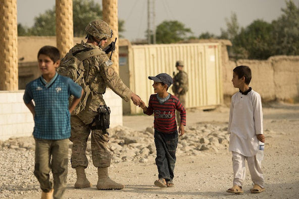 "Staff Sgt. Michael Sweeney greets a local Afghan youth June 13, 2013, during a security detail in the town of Saka near Bagram Airfield, Afghanistan. Security forces Airmen teamed up with 577th Expeditionary Prime Base Engineer Emergency Force Squadron pavement and heavy equipment ""Dirt Boys"" to rebuild a road connecting Saka with Payan Janqadam. Sweeney hails from Clovis, Calif., and is deployed from the 144th Fighter Wing, California Air National Guard. (U.S. Air Force photo/Master Sgt. Ben Bloker)"