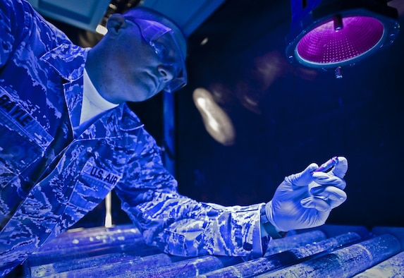 Staff Sgt. David Bayle inspects an aircraft pin for cracks under a black light after dipping the part into chemicals mixed to show cracks not normally visible to the naked eye Aug. 6, 2013, at the 379th Air Expeditionary Wing in Southwest Asia. Bayle is a 379th Expeditionary Maintenance Squadron nondestructive inspection craftsman deployed from Eielson Air Force Base, Alaska. (U.S. Air Force photo/Senior Airman Benjamin Stratton)