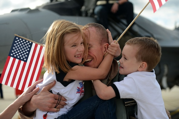 Maj. Greg Boland hugs his children Rylie and Carter after returning from a deployment Sept. 15, 2013, at Spangdahlem Air Base, Germany. Airmen assigned to the 480th Fighter Squadron train to provide decisive combat power to combatant commanders for contingency operations down range. Boland is a 480th Fighter Squadron pilot from Reading, Pa. (U.S. Air Force photo/Airman 1st Class Gustavo Castillo)