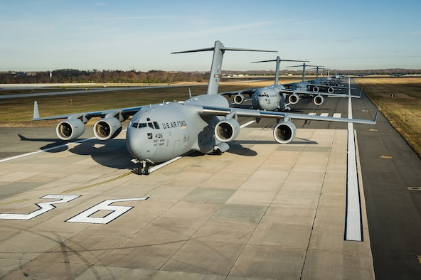 "Twelve KC-10 Extenders and six C-17 Globemaster IIIs from the 305th Air Mobility Wing perform an ""elephant walk,"" as part of a training exercise Nov. 21, 2013, at Joint Base McGuire-Dix-Lakehurst, N.J. The exercise enabled aircrew, maintenance, command post and operational support personnel to test their ability to launch a mass amount of aircraft in support of real-world operations. An elephant walk is a nose-to-tail taxi formation. (U.S. Air Force photo/Russ Meseroll)"