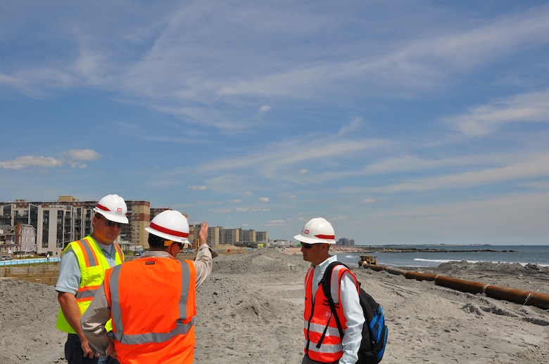 U.S. Army Corps of Engineers personnel discuss beach renourishment activities at the site of active sand placement work in the Rockaways August 15, 2013. Post-Sandy sand placement activities are underway at Rockaway Beach in Queens, NY as part of a project placing roughly 3.5 million cubic yards onto the beach to help reduce risks from future storms.