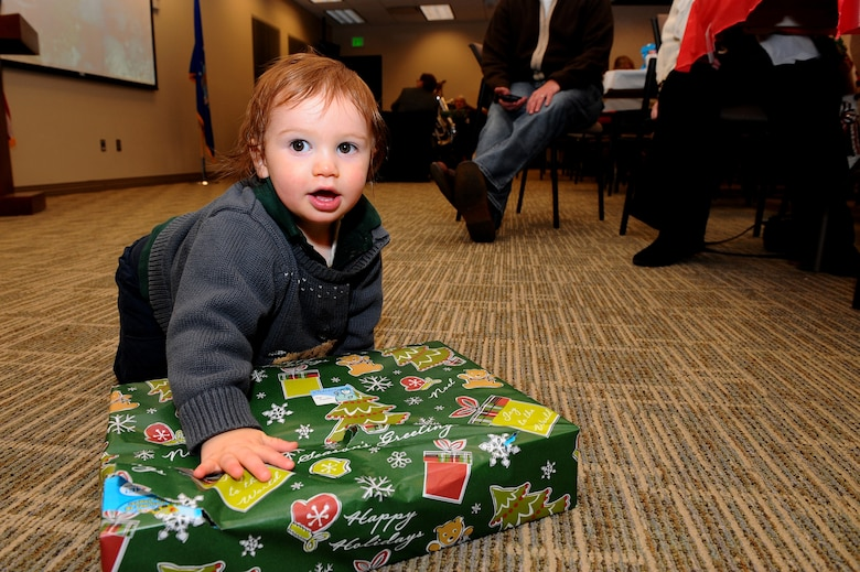 Theodore rips off the wrapping on a gift Dec. 20, 2013, at the chapel on Buckley Air Force Base, Colo. The gathering is an event that allows the families of deployed-servicemembers to meet with and enjoy the company of others. The holiday celebration included a catered dinner, presents for the children, live music and several door prizes. (U.S. Air Force photo by Senior Airman Phillip Houk/Released)