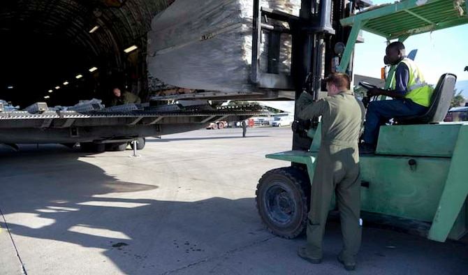Tech. Sgt. William Hyde and Staff Sgt. Doug Tadevich help a Haitian citizen offload a pallet onto a forklift Dec. 19, 2013, at Port-au-Prince, Haiti. Airmen assigned to the 97th Air Mobility Wing delivered 136,000 pounds of rice, beans and corn meal that will be distributed to various orphanages in Haiti. Hyde is a 58th Airlift Squadron student training management flight chief and Tadevich is a 58th loadmaster instructor. (U.S. Air Force photo/Airman 1st Class Klynne Pearl Serrano)