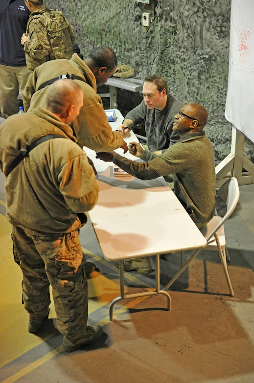 Comedians Rob Maher and Tommy Davidson sign autographs after their show at Bagram Airfield, Afghanistan, Dec. 31, 2013. The two performed a comedy routine for deployed Service members on New Year's Eve.(U.S. Air Force photo by Senior Master Sgt. Gary J. Rihn/Released)