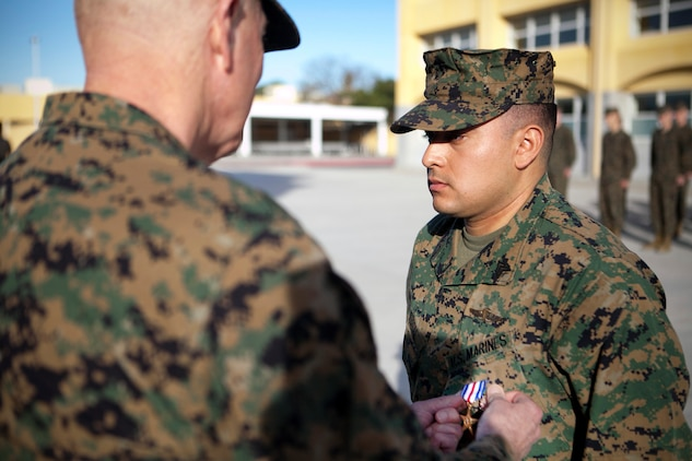 MARINE CORPS RECRUIT DEPOT, SAN DIEGO -- Lt. Gen. Steven A. Hummer, commander of Marine Forces Reserve and Marine Forces North, pins a Silver Star Medal on Sgt. Miguelange G. Madrigal, a radio chief with Supporting Arms Liaison Team G, 1st Air Naval Gunfire Liaison Company, I Marine Expeditionary Force Headquarters Group, aboard Marine Corps Recruit Depot, San Diego, Jan.  31, 2013. Madrigal, a native of Bakersfield, Calif., was awarded the nation's third highest honor for his actions as a member of a squad patrol that was pinned down by insurgent fire. On Feb. 15, 2010, he repelled an enemy attack, rushed to save a fellow Marine, called in multiple fire-support missions, and called in a casualty evacuation. (U.S. Marine Corps photo by Cpl. Marcin Platek/Released)