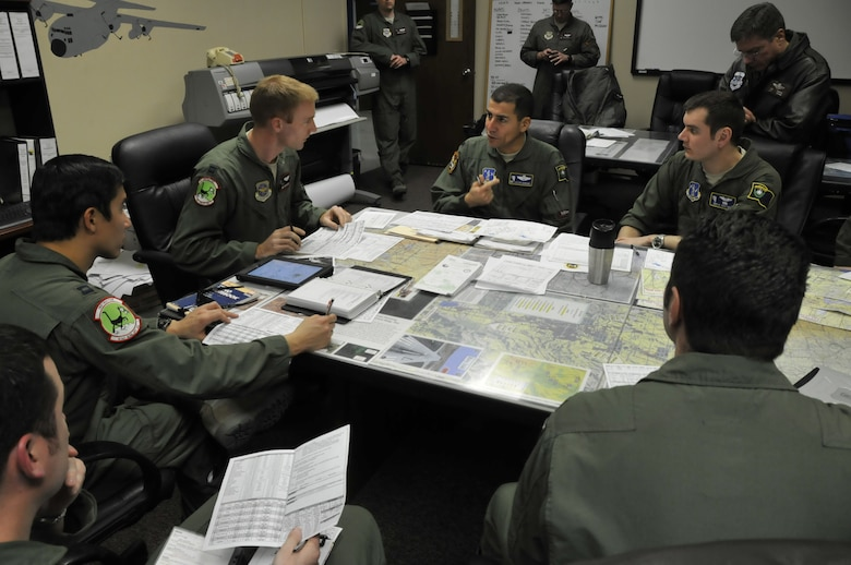 Lt. Col. Caesar Garduno commander of the 192nd Airlift Squadron (center, right) discussing operations with Capt. Jim Hodgson (center, left) along with other members of the 192nd and 41st Airlift Squadrons prior to flying an interfly mission around northern Nevada. The 41st Airlift Squadron was in Reno to practice mountain flying and to conduct other training prior to deploying to Afghanistan (USAF photo by Tech. Sgt. Eric Ritter released).