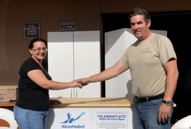 Mr. Jeff Taylor, an employee of Akzo Nobel Coatings, delivers donated furniture to Nicola Thompson, Airman's Attic volunteer, Jan. 25, 2013 at the Nellis Air Force Base Airman's Attic.  The Aiman's Attic is a non-profit organization run by volunteers supplying E-4's and below with no-cost household items. (U.S. Air Force photo by Tech Sgt. Taylor Worley)