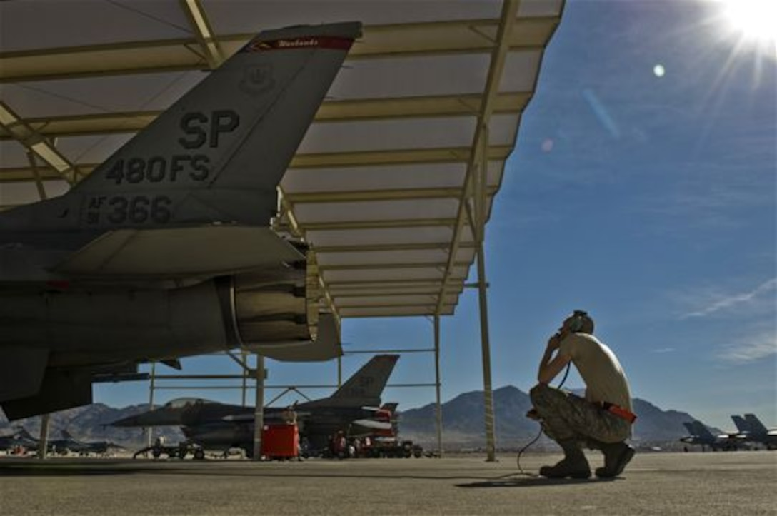 Airman 1st Class Daniel Lasal performs preflight checks on an F-16 Fighting Falcon during Exercise Red Flag 13-2 Jan. 22, 2013, at Nellis Air Force Base, Nev. Lasal watches the engine and talks to the pilot as he puts the engine though its preflight inspection. Lasal is a crew chief assigned to the 480th Aircraft Maintenance Unit at Spangdahlem, Air Force Base, Germany, (U.S. Air Force photo/Senior Airman Daniel Hughes)