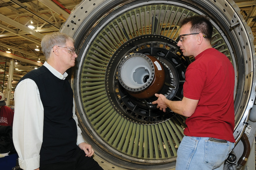 Reaping positive benefits of the relationship between the Air Force Life Cycle Management Center and the Air Force Sustainment Center, engineers and mechanics work to quickly resolve any repair issues during production here at Tinker. In Bldg. 9001's F108 Navy/Air Force engine shop, aerospace engineer Michael Denny, left, and engine mechanic Rick Thompson discuss the life cycle fatigue and possible routine maintenance requirements of the number 1-2 bearing support. (Air Force photo by Margo Wright)