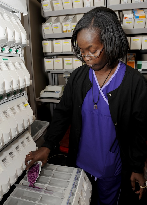 Terri Savage-Campbell, 2nd Medical Support Squadron pharmacy technician, refills a dispenser at the base pharmacy on Barksdale Air Force Base, La., Feb. 4. The medication dispenser contains more than 100 prescription drugs that are commonly prescribed. This machine allows fast and accurate distribution of medication. (U.S. Air Force photo/Airman 1st Class Benjamin Gonsier)
