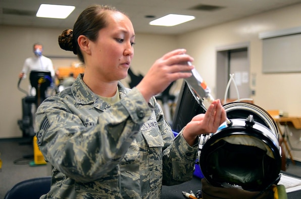 Staff Sgt. Suzzett Stalesky, 9th Physiological Support Squadron launch and recovery technician, demonstrates the use of tube food by inserting it into the feeding port of a U-2 full pressure suit helmet at Beale Air Force Base, Calif., Feb. 5, 2013. The U-2 is the only aircraft in the Department of Defense inventory that requires the utilization of a full pressure suit. (U.S. Air Force photo by Airman 1st Class Drew Buchanan/Released)