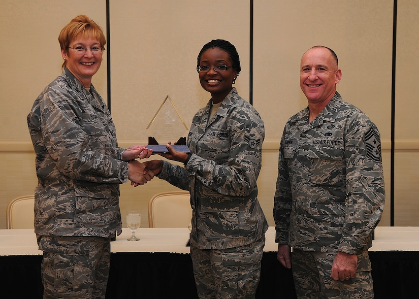 Colonel Judith Hughes, 628th Medical Group commander, and Chief Master Sgt. Al Hannon, 628th Air Base Wing command chief, recognize Airman 1st Class Amber Shepherd, 628th MDG patient travel medical technician, as a Diamond Sharp award winner during a ceremony at the Charleston Club, Feb. 4, 2013, at Joint Base Charleston - Air Base, S.C. Diamond Sharp awardees are Airman chosen by their first sergeants for their excellent performance. (U.S. Air Force photo/ Staff Sgt. Rasheen Douglas)