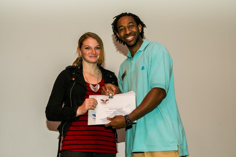 Allison Meyerhoff accepts an award from Lamar Moorehead, Youth Programs teen coordinator, during the Youth Programs Volunteer Recognition Ceremony Jan. 30, 2013, at Joint Base Charleston - Weapons Station, S.C. Meyerhoff volunteered 288 hours as a Junior Staff Volunteer with the School Age Summer Camp Program. More than 15 members from Team Charleston's community were honored during the ceremony. (U.S. Air Force photo/ Senior Airman George Goslin)