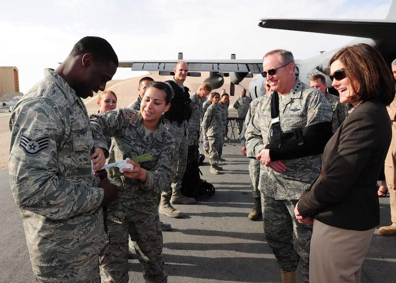 "SOUTHWEST ASIA -- Senior Airman Alexia Briant, 379th Expeditionary Medical Group, demonstrates the use of a combat dressing from an Individual First Aid Kit to Air Force Chief of Staff Gen. Mark A. Welsh III and his wife, Betty, during a tour of the 379th Air Expeditionary Wing. The visit was highlighted by a tour of the facilities and talks with the Airmen of the ""Grand Slam"" Wing about their jobs, deployment and families. (U.S. Air Force photo/Master Sgt. Brendan Kavanaugh)"