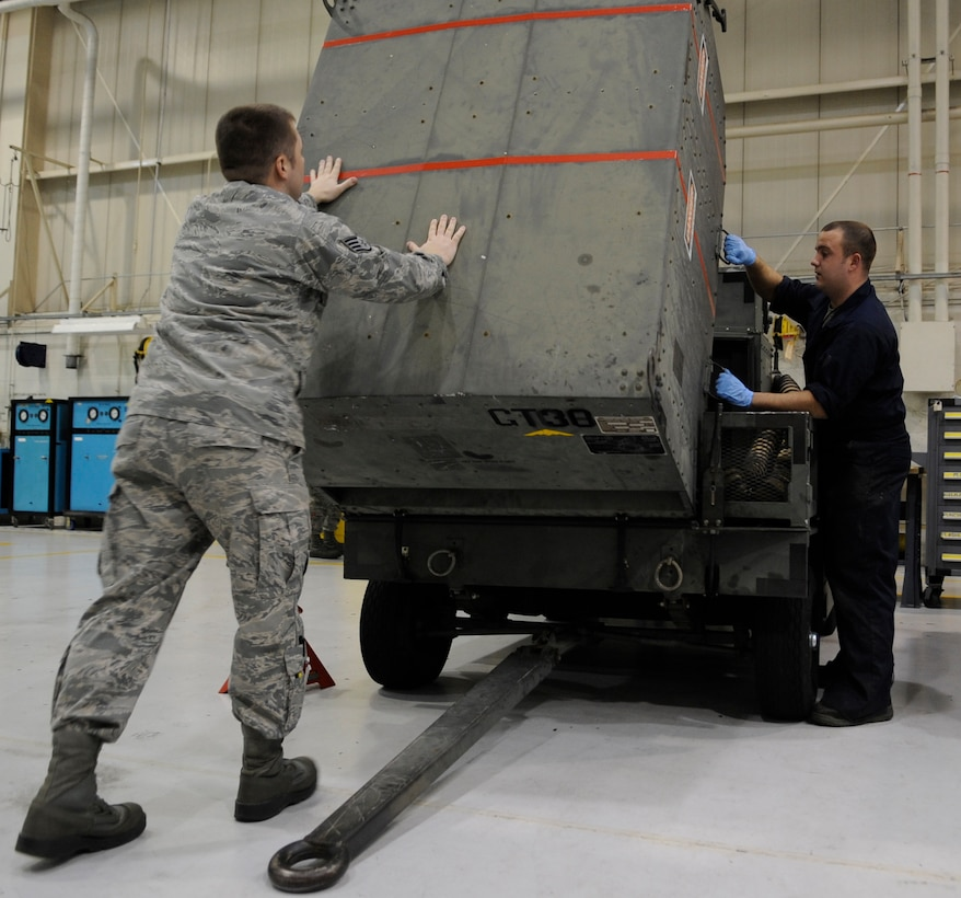 WHITEMAN AIR FORCE BASE, MO. – Staff Sgt. Calvin Grosz and Cole Adams, 509th Maintenance Squadron aerospace ground equipment mechanics, lift the top off of a -95 air start cart gas turbine compressor for routine maintenance here Jan. 31. The gas turbine is an internal combustion engine that uses air as the working fluid. (U.S. Air Force photo/Staff Sgt. Alexandra M. Boutte) (RELEASED)
