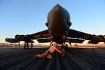 Air Force Senior Airman John Myer pushes a tow bar under the tire of a B-52H Stratofortress at Nellis Air Force Base, Nevada.