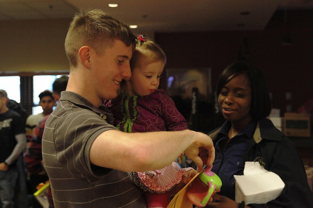 Lance Cpl. Spencer Holm, Marine Fighter Attacks Squadron 251, aviation avionics technician, opens a prize with his daughter during the units family day at afterburners, Feb. 1. Family days are organized to improve overall troop morale and build camaraderie between service members, leadership and families.