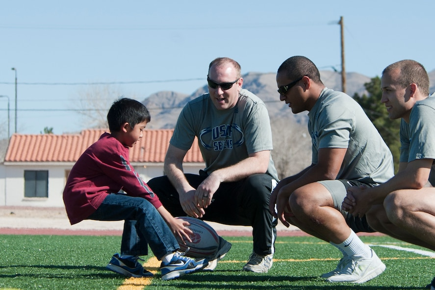 A Lomie Heard Elementary School student practices sprinting drills as Air Force Rugby Sevens players look on during a children's rugby clinic Feb. 6, 2013, at Nellis Air Force Base, Nev.  Armed forces Rugby Sevens teams from all four branches of service are participating in the largest amateur rugby tournament in Las Vegas. (U.S. Air Force photo by Lawrence Crespo)