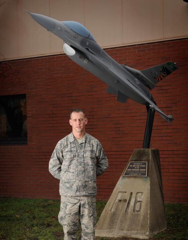 Tech. Sgt. Michael Goulette, a structural repair specialist with the 180th Fighter Wing, Ohio Air National Guard, with the F-16 static display in front of the 180th Fighter Wing Operations building.