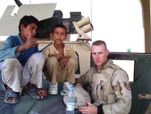"""U.S. Air Force Tech. Sgt. Francis Woznick, 366th Security Forces Squadron, and two Iraqi children take a break on the hood of his Humvee. Woznick said he remembers well the day he responded to a traffic accident to find an Iraqi boy dying. """"He turned grey in front of me,"""" said Woznick, who has no children of his own but he often thinks of his younger sister who still lives at his childhood home in Seneca Falls, N.Y. """"There was nothing I could do."""" (Courtesy photo)"""