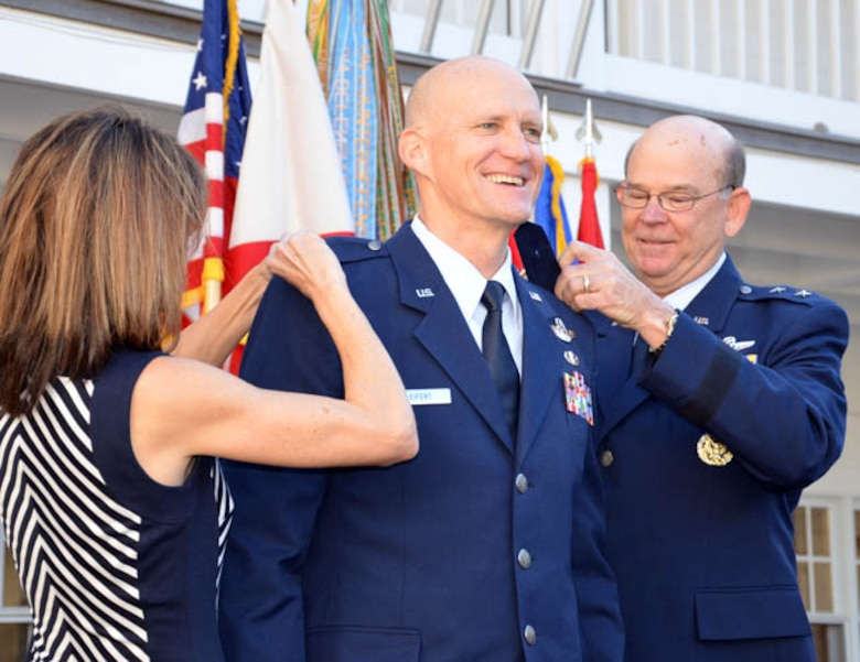"""Col. James Eifert (center) is promoted to the rank of brigadier general and officially """"pinned"""" by his wife Beth and the Adjutant General of Florida Maj. Gen. Emmett Titshaw Jr. during a ceremony in St. Augustine, Fla., Feb. 8, 2013. Concurrently Eifert assumed the position of Assistant Adjutant General for Air and Deputy Commander of the Florida Air National Guard. Photo by Master Sgt. Thomas Kielbasa"""