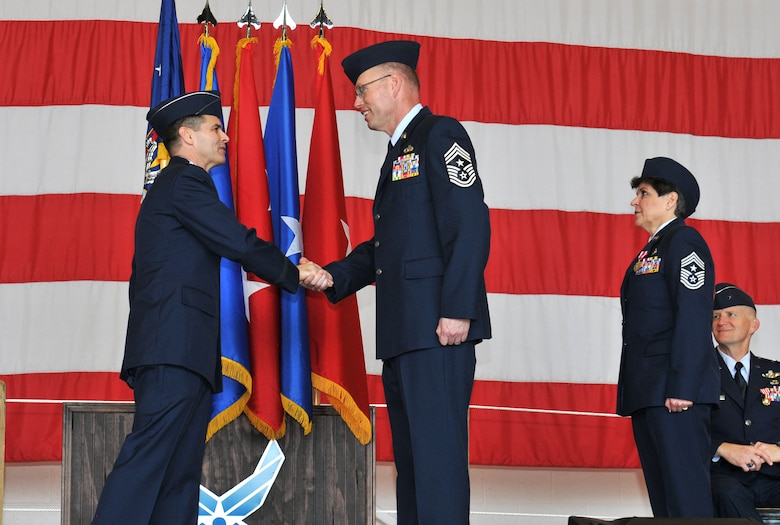 Col. Brian Simpler (left), Commander, 125th Fighter Wing, passes the unit coin to newly appointed 125th Fighter Wing Command Chief, Chief Master Sgt. Mike Seger at a Change of Authority Ceremony here February 10, 2013. Chief Master Sgt. Seger follows former Command Chief Sharon Ervin (right), who spent six years as the 125th Fighter Wing Command Chief Master Sgt. (USAF Photo by MSgt. Shelley Gill)