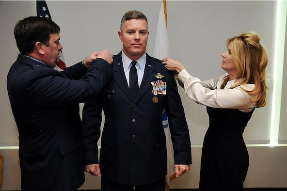 Brig. Gen. Gary Keefe, commander, Massachusetts Air National Guard, and Aprile Brooks pins the rank of Brigadier General on the uniform of Robert Brooks Jr., during a promotion ceremony at the Massachusetts National Guard's Joint Force Headquarters building, Hanscom Air Force Base, Bedford, Mass., Jan. 25, 2013. Brooks serves as the Assistant Adjutant General- Air, Massachusetts Air National Guard.