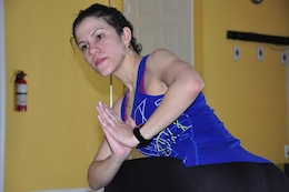 Sgt. Yari Kobus holds a twisted warrior pose after leading a 90-minutelong Hot Yoga class at the Stafford House of Yoga in Stafford on Jan. 26.