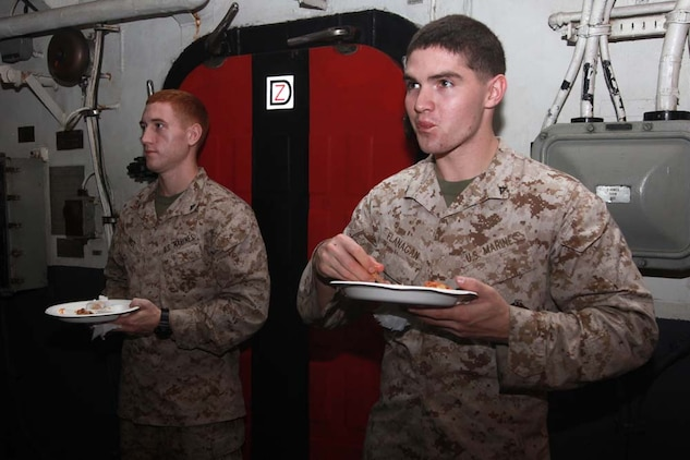 Lance Cpls. Micah A. Host (left), rifleman, Kilo Company, Battalion Landing Team 3/5, and Brian L. Flanagan, field radio operator, Command Element, both with 15th Marine Expeditionary Unit, eat pizza and chicken wings during the Super Bowl party held in the hangar bay of the USS Peleliu, Feb. 4. The ship hosted a Super Bowl party for its Marines and sailors as a way to help them decompress and enjoy some of the comforts of home while being forward deployed. The 15th MEU is deployed as part of the Peleliu Amphibious Ready Group as a U.S. Central Command theater reserve force, providing support for maritime security operations and theater security cooperation efforts in the U.S. 5th Fleet area of responsibility. Host, 23, is from Hartselle, Ala., and Flanagan, 22, is from Columbus, Ohio.