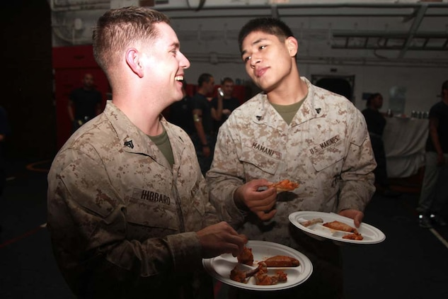Corporals Christopher W. Hibbard (left), assessment consequence management team member, Chemical Biological Radiological Nuclear Defense Detachment, and Jose M. Mamani, supply clerk, both with the Command Element, 15th Marine Expeditionary Unit, eat chicken wings during the Super Bowl party held in the hangar bay of the USS Peleliu, Feb. 4. The ship hosted a Super Bowl party for its Marines and sailors as a way to help them decompress and enjoy some of the comforts of home while being forward deployed. The 15th MEU is deployed as part of the Peleliu Amphibious Ready Group as a U.S. Central Command theater reserve force, providing support for maritime security operations and theater security cooperation efforts in the U.S. 5th Fleet area of responsibility. Hibbard, 25, is from Mexia, Texas, and Mamani, 21, is from Burke, Va.