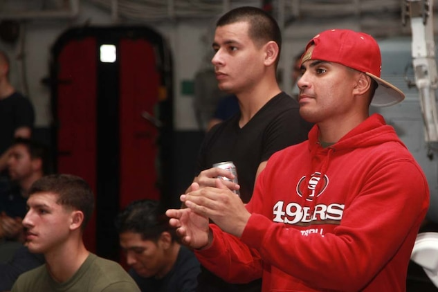 Sergeant William A. Bonilla (right), assessment consequence management team member, Chemical Biological Radiological Nuclear Defense Detachment, and Lance Cpl. Alberto Perez III, administrative specialist, both with the Command Element, 15th Marine Expeditionary Unit, watch Super Bowl XLVII during the Super Bowl party held in the hangar bay of the USS Peleliu, Feb. 4.  The ship hosted a Super Bowl party for its Marines and sailors as a way to help them decompress and enjoy some of the comforts of home while being forward deployed. The 15th MEU is deployed as part of the Peleliu Amphibious Ready Group as a U.S. Central Command theater reserve force, providing support for maritime security operations and theater security cooperation efforts in the U.S. 5th Fleet area of responsibility. Bonilla, 26, is from Houston, and Perez, 21, is form Burbank, Calif.