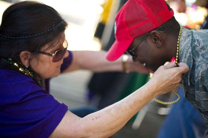 Senior Airman Lavelle Ali, 823rd RED HORSE, right, receives a bead necklace from a local resident after a mardi gras parade at Navarre Beach, Fla., Feb. 2, 2013. Hurlburt Field Airmen participated in the event to foster ties with the Emerald Coast community. (U.S. Air Force photo / Tech. Sgt. Vanessa Valentine)