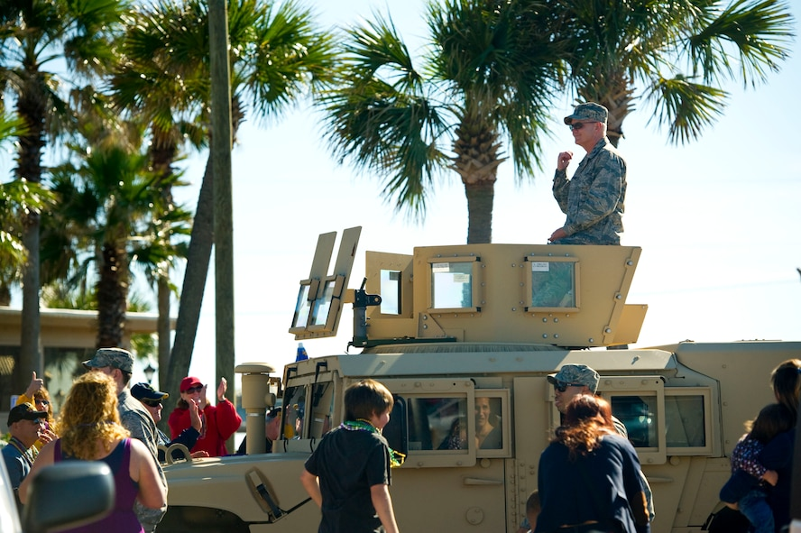 Col. Troy Molnar, commander of 1st Special Operations Medical Group, rides atop a High Mobility Multipurpose Wheeled Vehicle during a mardi gras parade at Navarre Beach, Fla., Feb. 2, 2013. Molnar was accompanied by a dozen volunteers from Hurlburt Field who walked alongside the vehicle in the parade. (U.S. Air Force photo / Tech. Sgt. Vanessa Valentine)