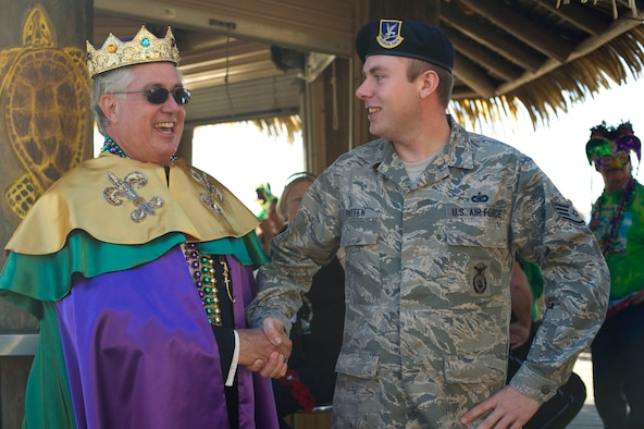 Peter Peterzen, king of the 2013 Navarre Krewe of Jesters, left, shakes hands with Staff Sgt. Alex Patten, 1st Special Operations Security Forces Squadron, right, after a mardi gras parade at Navarre Beach, Fla., Feb. 2, 2013. Patten drove a High Mobility Multipurpose Wheeled Vehicle as part of Hurlburt Field's entry in the parade. (U.S. Air Force photo / Tech. Sgt. Vanessa Valentine)