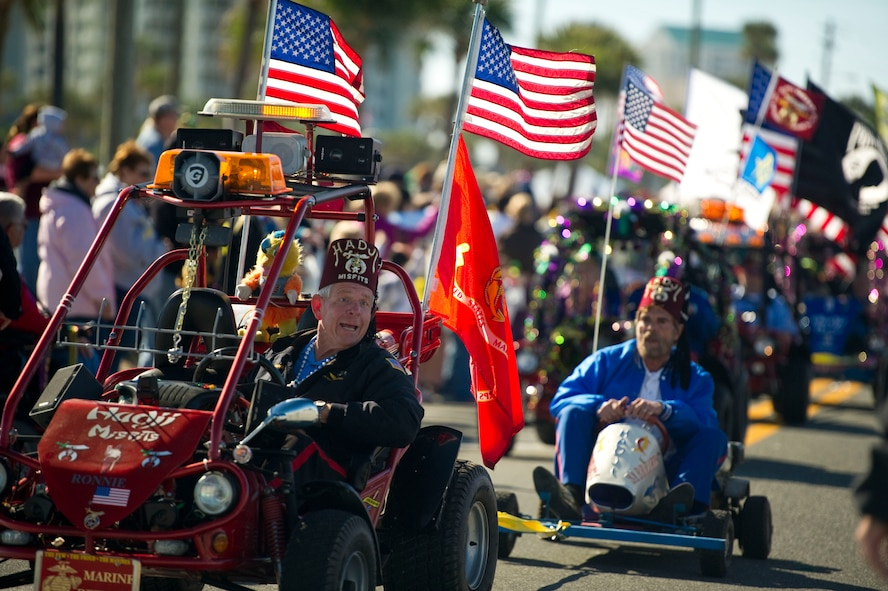 Member of the Hadji Misfits, a local group of the Shriners, ride carts bearing flags along a parade route during a mardi gras parade at Navarre Beach, Fla., Feb. 2, 2013. Several entries competed for winning best entry in the parade. (U.S. Air Force photo / Tech. Sgt. Vanessa Valentine)