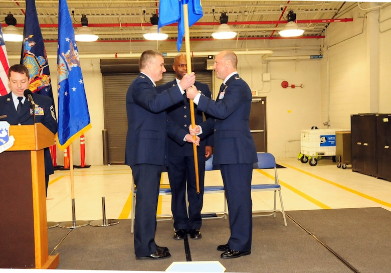 Col. John Higgins, the commander of the 107th Airlift Wing hands the Operations Group flag to Col.  Michael  Bank as he assumes command of the Operations Group at the Niagara Falls Reserve Station on Feb, 10, 2013 (Air National Guard Photo/Senior Master Sgt. Ray Lloyd)