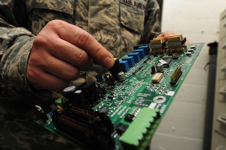WHITEMAN AIR FORCE BASE, Mo. -- Staff Sgt. Clint Smith, 509th Civil Engineer Squadron electrical systems craftsman, checks to see if a circuit board is in operable condition, Jan. 29. Visually inspecting circuit boards for defects and damage is part of the routine maintenance electricians perform on electrical systems every day. (U.S. Air Force photo/Staff Sgt. Nick Wilson) (Released)