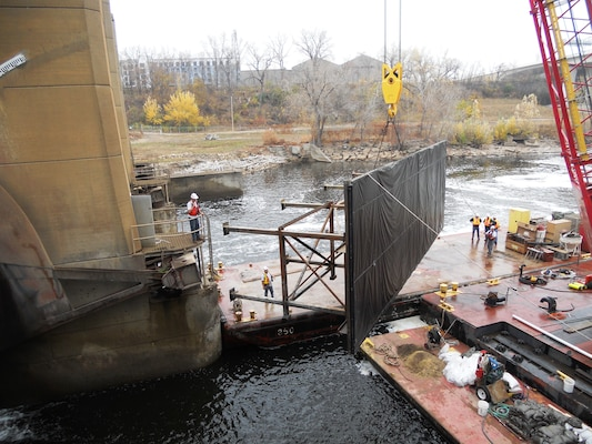 District maintenance and repair employees place a temporary dam, or cofferdam, on the Lower St. Anthony Falls Lock and Dam in Minneapolis during repairs in the fall of 2012.